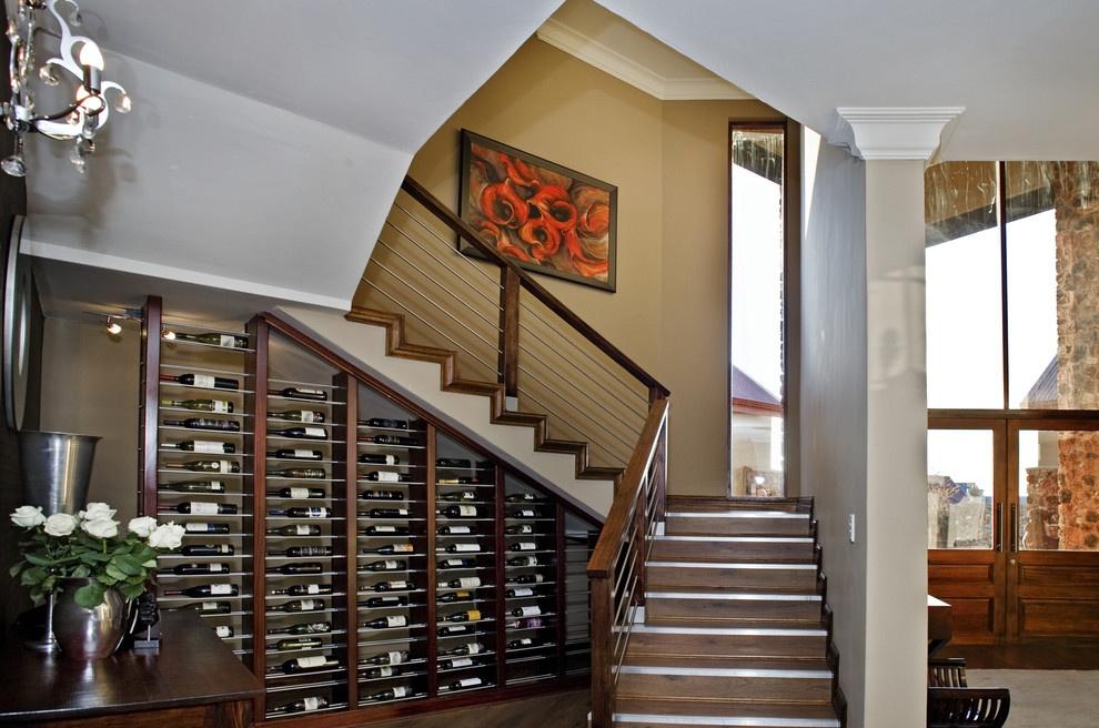Винный шкаф под лестницей в гостиной
